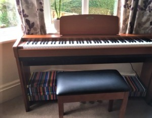 Margaret's electric piano in the window with a view of the hedge in the garden in the background