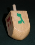 A photo of a wooden dreidel showing two of four sides, the handle and rounded base for spinning it.  One side has a green Hebrew letter, the other has a red letter.