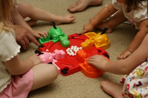 A photo of children crowded round a game of Hungry Hippos.  Four brightly coloured plastic hippos surround the hollow containing white balls.  The children have to catch the balls with the hippos mouths, opened by a lever on their tails.