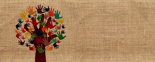 A painting of a tree with handprints for leaves, in many different colours, on a hessian background.