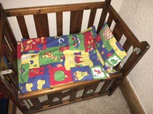 Linda's toy cot made from polished wooden bars, with the side dropped. Inside there is a red, yellow blue and green toy duvet and pillow with pictures of an apple, bear, car, ducks etc. used to teach the alphabet.
