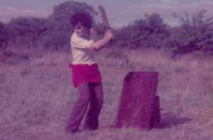Curly haired Tony as a young teenager with his cricket bat raised ready to hit the ball, in front of a homemade wicket made from a piece of metal leaning against a post.  He is wearing a white shirt with sleeves rolled up, brown flared trousers and a red jumper tied round his waist.