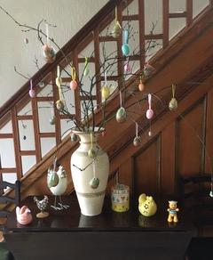 Linda's Easter display.  A tall vase on a table contains the bare branch decorated with pink, blue and gold eggs. Around the vase are a selection of china hens of differing sizes and a china teddy bear.