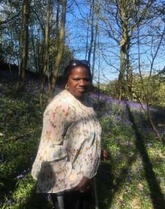 Pauline standing in the Spring sunshine wearing her favourite dress, with bluebells, bare trees and bright blue sky in the background.