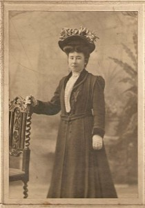 A sepia studio photograph of a young woman dressed in a long, fur trimmed long winter coat with a belt round the middle.  She is wearing white gloves and is posed with one hand on the back of an ornately carved wooden chair.  Her hair is neatly piled on top of her head, crowned by a huge hat with artificial flowers on top.