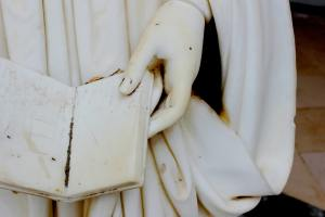 A detail of a white marble statue showing a hand holding an open book.