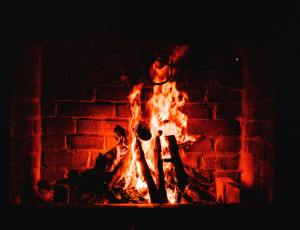 A roaring fire lighting up the brick fireplace behind it with a warm red glow