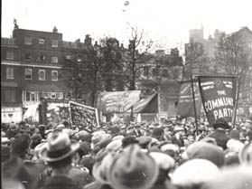 A photograph of a crowd taken from behind, showing the heads of men wearing hats and many banners held aloft, including one from The Communist Pary