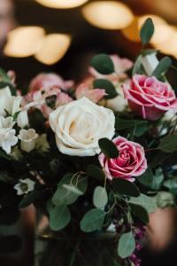 A flower arrangement of beautiful pink and white roses with foliage, with a soft focus behind showing the ceiling lights of a church