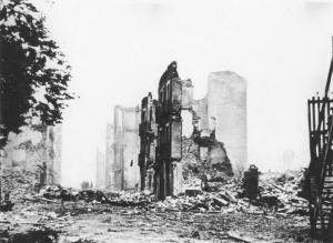 An archive photograph of the aftermath of the bombing of Guernica, showing only the frontages of buildings left standing on a rubble-filled street.