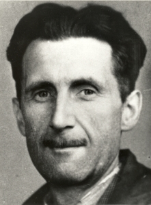 A photograph of George Orwell's face looking directly into the camera, taken from his National Union of Journalists membership card