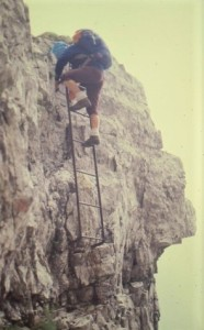 Margaret is coming backwards down a  metal ladder on a vertical rock face.