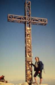 Margaret is standing next to a metal cross four times as high as herself, with two men seated nearby looking out over the view from the top of the very high mountain.