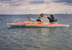 A bright red canoe on a choppy blue sea, containing a small boy seated in the front with his mother, Margaret, behind. They are raising their paddles and look as though they are synchronising their strokes well. It is  a bright sunny day, although there are white clouds in the blue sky.