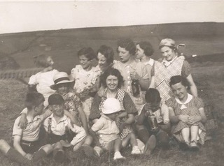 A black and white photograph of women and children, some wearing sun hats, sitting in a field