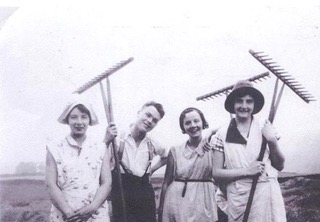 A black and white photo of three smiling young women, all wearing dresses and sun hats, and a young man in trousers with braces.  They are each holding aloft the tools they have been using.
