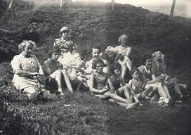 A black and white photograph of the family group sitting on the grass in front of a dry stone wall