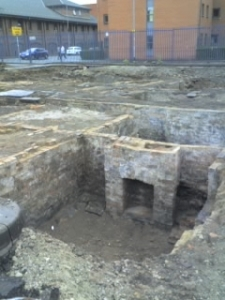The excavations showing a fireplace in a cellar in a brick-built square room, part of a street of similar houses. Modern university buildings are visible in the background, behind a high fence.