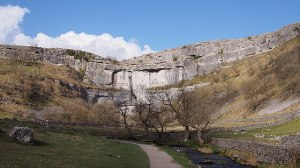 A view of the vertical cliff face of Malham Cove, showing the path besides the stream towards it.  Besides the path, there is a small boulder.