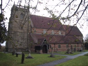 The church has a stone built tower and attractive red and yellow brick work with a red slate roof.  Old gravestones are visible in the foreground, amidst a lawn.